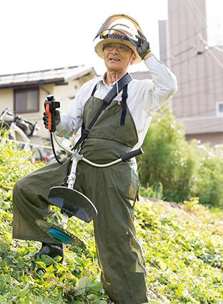 自宅近くの柿川土手の草を刈る河内さん。「戦時中、長岡が空襲された際、多くの人が飛び込んで亡くなった柿川の美化活動を行うための助成金をいただき、備品を購入できました」