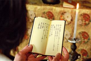 自宅の仏前で、母親のキヨヱさんと聖経『甘露の法雨』を読誦