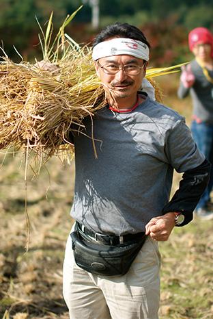 刈り取った稲を担ぐ、代表理事の曽根原久司さん NPO法人「えがおつなげて」│山梨県北杜(ほくと)市 取材/原口真吾(本誌) 写真/「えがおつなげて」提供