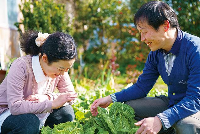 自宅の隣にある畑で。夫の秀治さんが久世さんに指先から指先へてんとう虫を渡すと、2人は顔を見合わせて微笑んだ