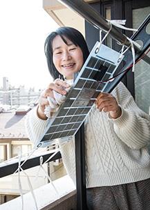 ベランダの物干し竿にひもで固定して設置されたミニ太陽光発電パネル