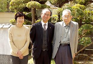 自宅の前で、妻の由実さん、養父の隆さんと。隆さんも熱心な生長の家の信仰者だ