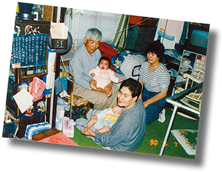 幼い頃の亜衣さん(中央奥)を抱く、曾祖父の岡川勝蔵さん。手前は曾祖母のヂョウさん、右は亜衣さんの母親の久美子さん
