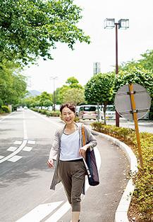 ヨガマットを肩に掛け、軽快な足取りで通りを歩く川島さん