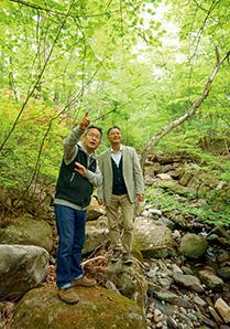 新緑が目に鮮やかな自宅近くの清里の森で、清里の自然の魅力について語る川嶋さん
