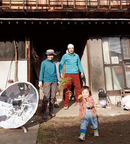 「ワールドカフェゲストハウス」│山梨県富士川町 取材/原口真吾 写真/堀 隆弘 ゲストハウスの玄関前で、山口宗一郎さん・博子さん親子。左にあるのは、調理に使うソーラークッカー