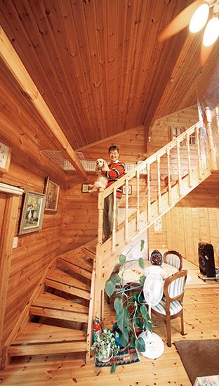 木の香りが漂う、洒落たログハウスの内部。ロフトに続く階段で愛犬とともに