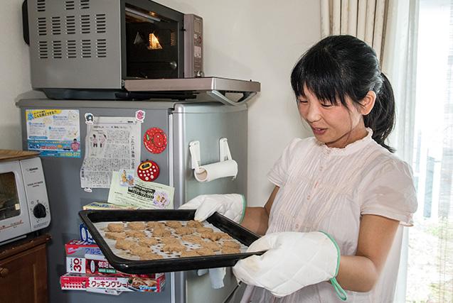 柿本真澄さん 34歳・山梨県北杜市 取材/南野ゆうり 撮影/野澤 廣 焼き上がったばかりのきなこクッキーを取り出す。バターの替わりににオリーブオイルを使っている