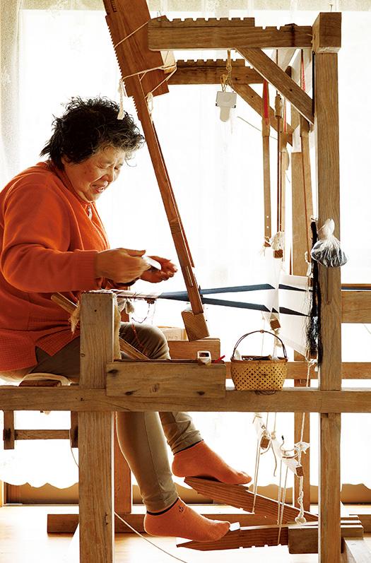 大島さん│75歳│鹿児島県喜界町 「織物を始めたのは65歳からですが、何事も遅すぎるということはないんですね」と、手慣れた様子で織機を動かす大島さん 取材/久門遥香(本誌) 写真/堀隆弘