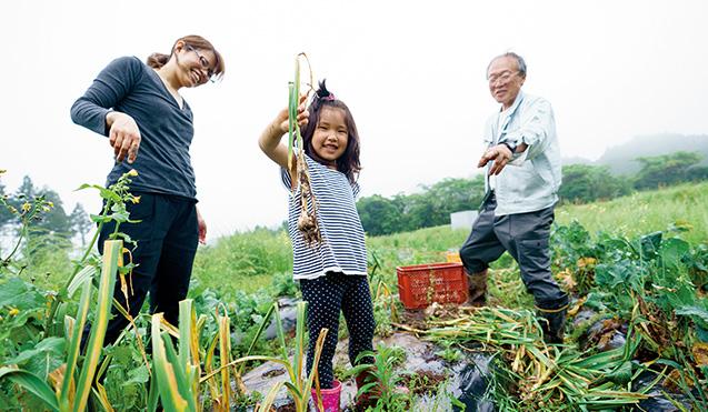 ニンニクの収穫を体験した川島さんと長女。大きく実ったニンニクを引き抜き、母娘2人の笑顔が弾けた