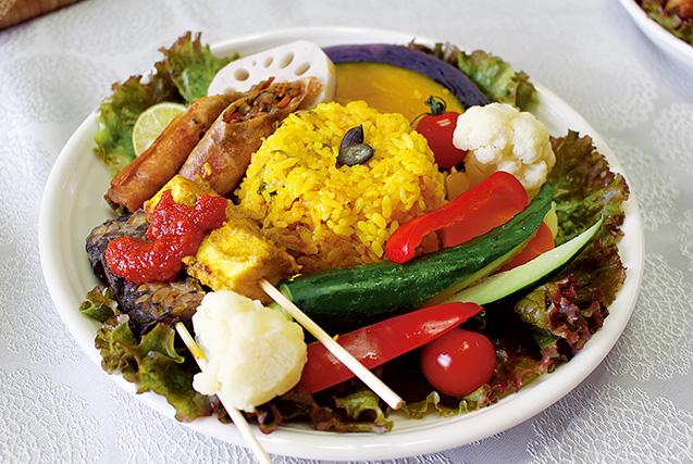 旬の野菜にピラフや春巻き、厚揚げの串焼きなどを盛りつけたノーミートのインドネシア料理