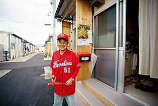 広島カープファンの吉川さん。赤い野球帽とユニフォームで、周囲の人たちを元気づけている
