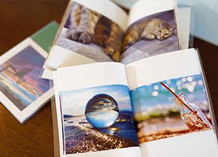 最新作を収めた閲覧用のアルバム。左下は水晶玉を使った写真、その上は、愛猫の「モモちゃん」を撮った写真