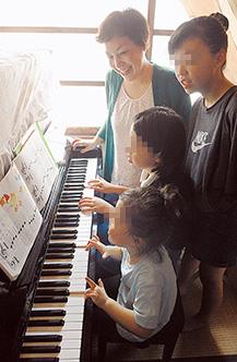 ピアノの練習の様子を見つめる和氣さん。「子どもたちの夢を、親として一所懸命、応援していきたいです」