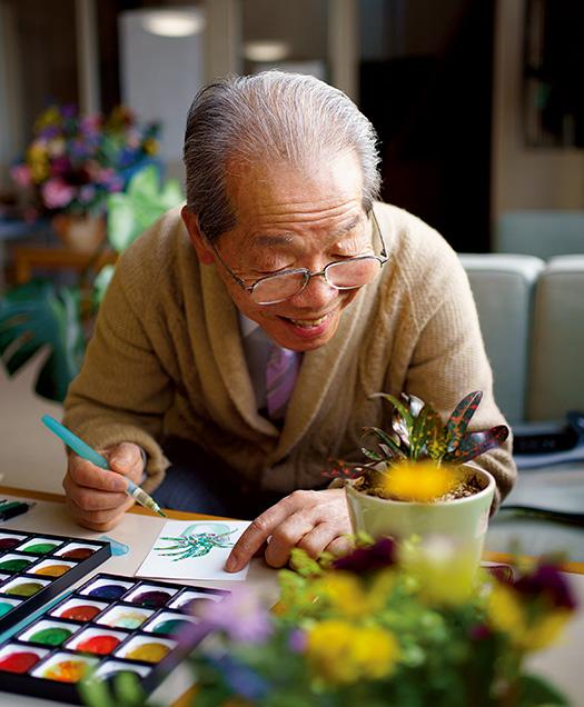 境 博(さかい・ひろし)さん│78歳│福岡県糸島市 テーブルにある観葉植物を眺めながら絵手紙を描く境さん。「没頭すると全てを忘れてしまいます」 取材/佐柄全一 写真/堀 隆弘