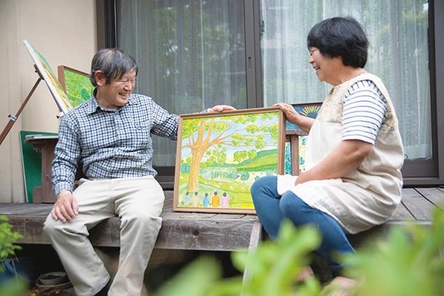 自宅の縁側で、妻の茂子さんと作品を眺めながら談笑する