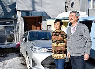 自宅前で妻の千波さんと。「家内も信仰してくれるようになって嬉しいです」
