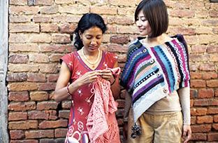 2012年、サフィア・ミニーさんと訪れたネパールのフェアトレード生産者団体「KTS」で。左の女性は、生産者のひとり(エシカル協会提供)