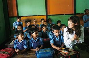 バングラデシュのフェアトレード生産者団体「タナパラ・スワローズ」の工房に併設されている小学校で子どもたちと。この小学校には、上記の団体で働く女性たちの子どもや地域の子どもたちが無料で通うことができる(エシカル協会提供)