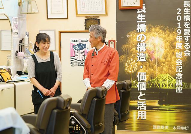 妻の恵子さんと。右後ろのポスター写真は、「小千谷市片貝まつり」で世界一の大玉を撮った木津さんの作品