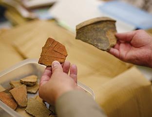 悠久の歴史を経てきた縄文時代の土器のかけらを手に